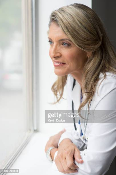 Caucasian doctor looking out window