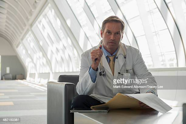 Caucasian doctor reading in lobby area