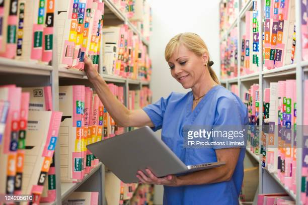 Caucasian doctor searching for medical record in file room with laptop