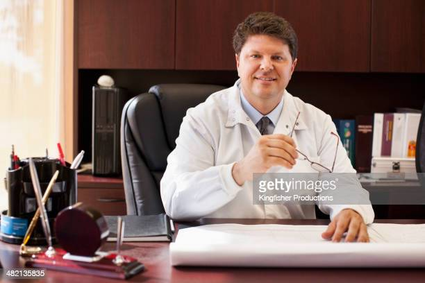 Caucasian doctor smiling at desk