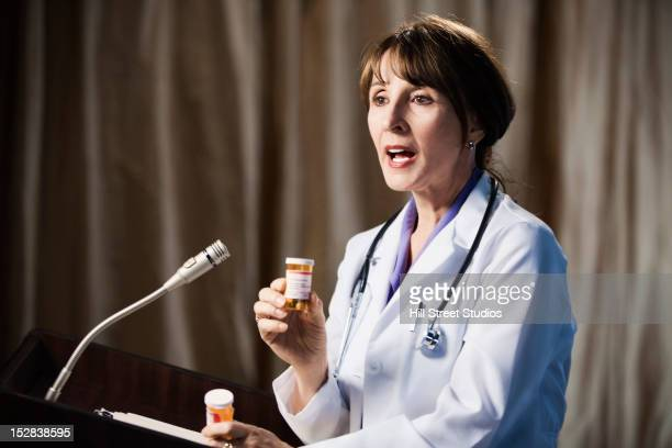 Caucasian doctor speaking at podium about medication