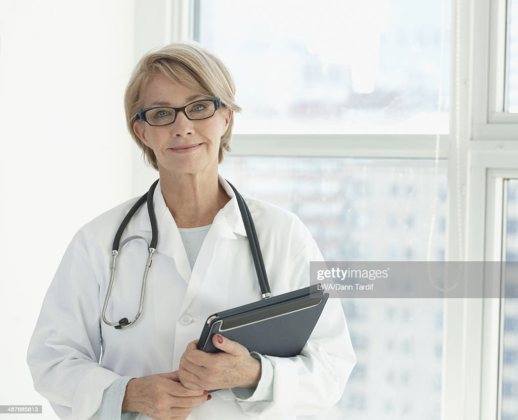 Caucasian doctor using digital tablet in hospital : Stock Photo