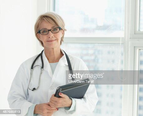 Caucasian doctor using digital tablet in hospital : Stock Photo