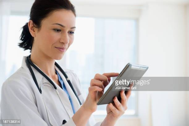 Caucasian doctor using tablet computer