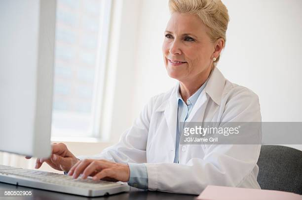 Caucasian doctor working at computer in office