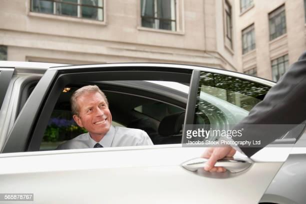 Caucasian driver opening car door for businessman