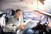 Caucasian driver reading magazine in autonomous car. Self driving vehicle. Driverless car.