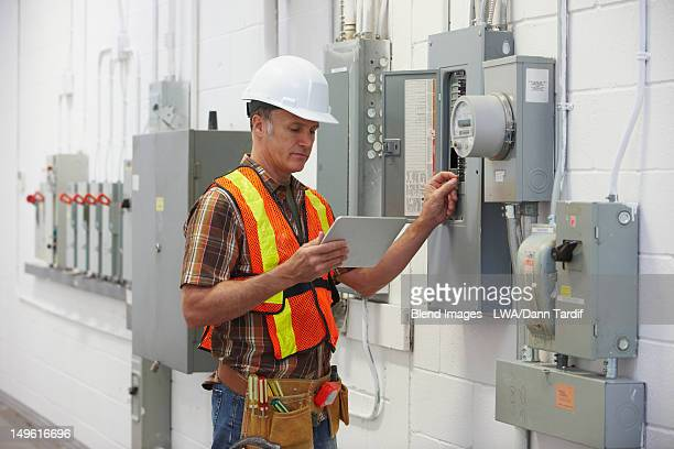 Caucasian electrician repairing fuse box and holding digital tablet
