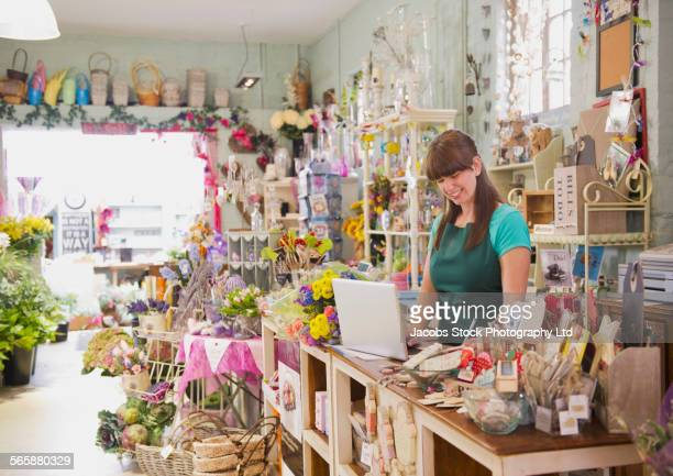 Caucasian employee working on laptop in gift shop
