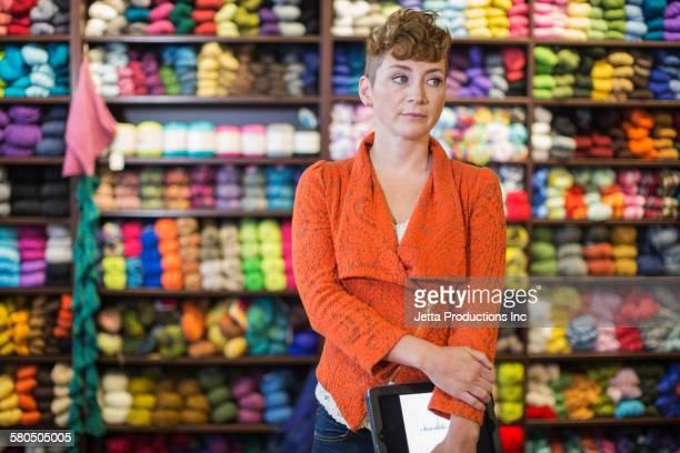 Caucasian entrepreneur holding digital tablet in yarn store