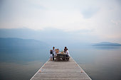 Caucasian family at picnic table on wooden dock over lake