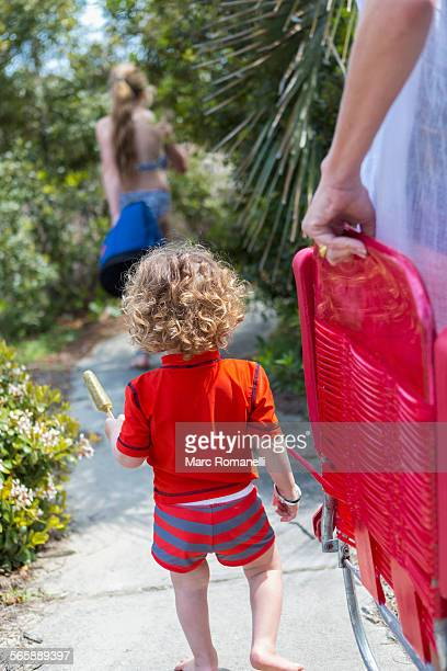 Caucasian family carrying deck chairs to beach