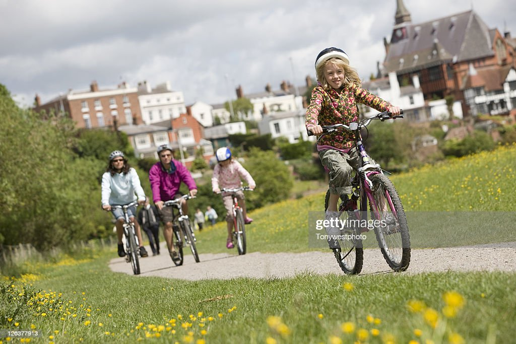 Caucasian family cycling in the Meadows, Chester, UK