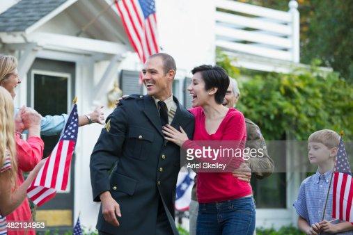 Caucasian family greeting returning soldier