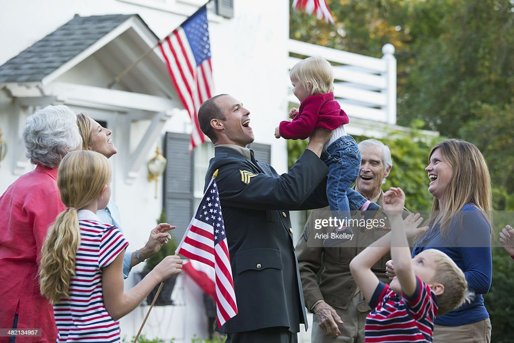 Caucasian family greeting returning soldier