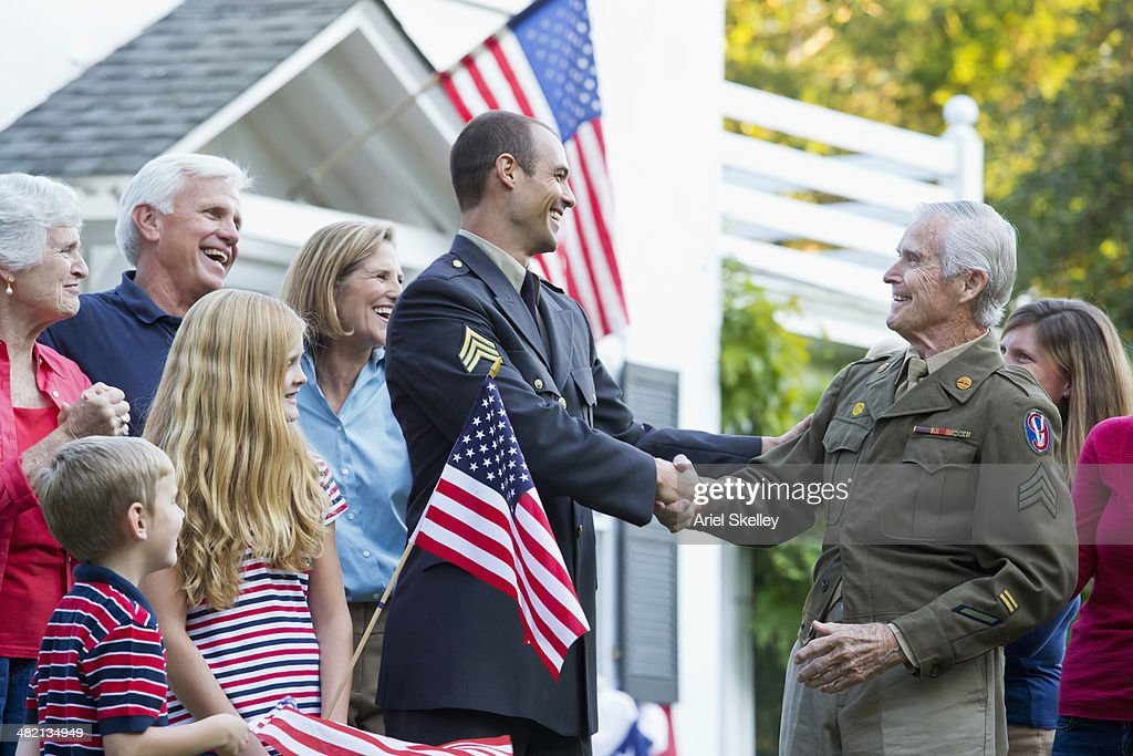 Caucasian family greeting returning soldiers