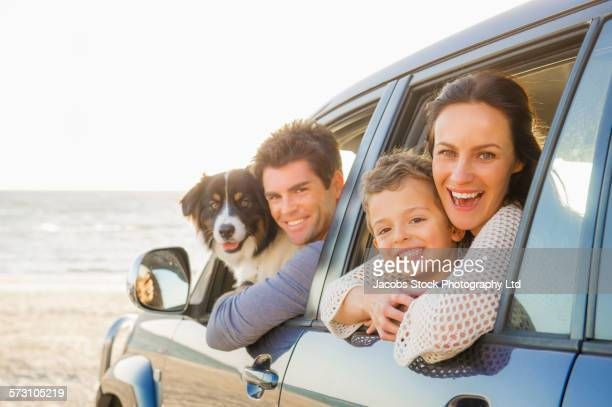 Caucasian family in car windows on beach