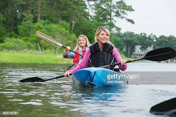 Caucasian family kayaking in river