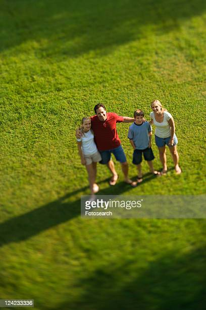 Caucasian family of four standing on lawn with arms around each other.