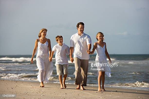 Caucasian family of four walking on beach.
