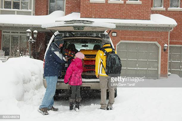 Caucasian family packing car in snow