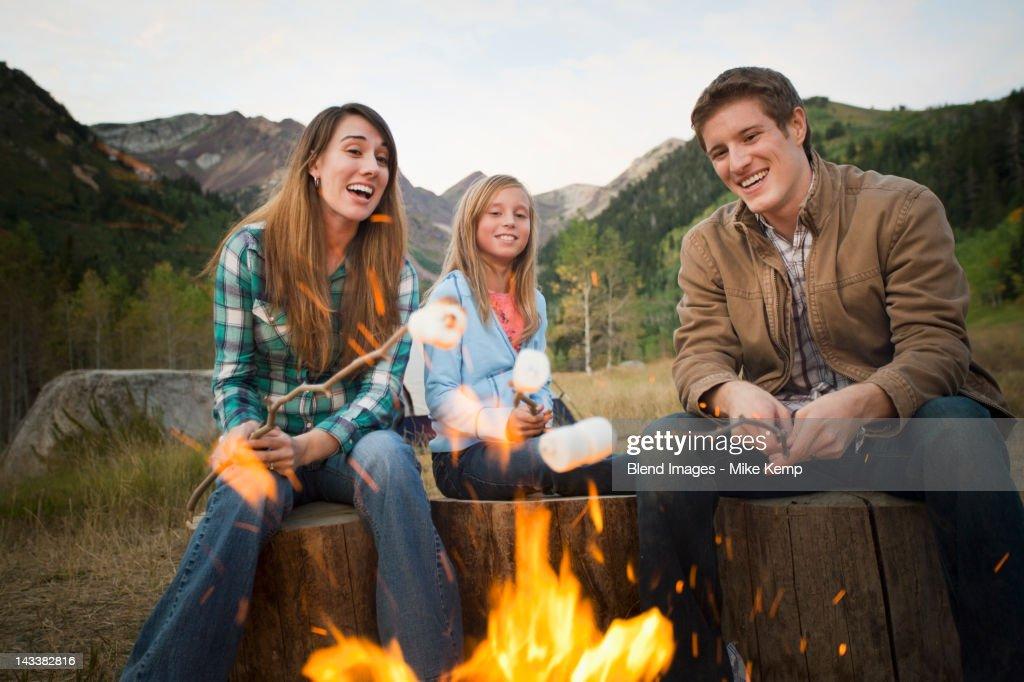 Caucasian family roasting marshmallows on campfire : Stock Photo