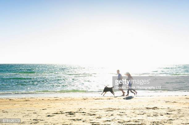 Caucasian family running with dog on beach