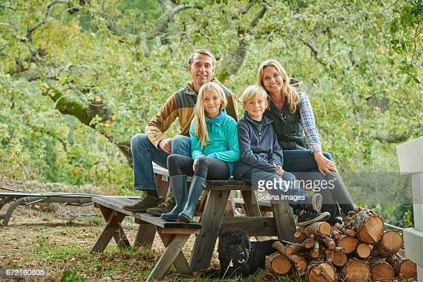 Caucasian family sitting on bench outdoors