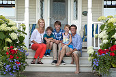 Caucasian family smiling on front porch