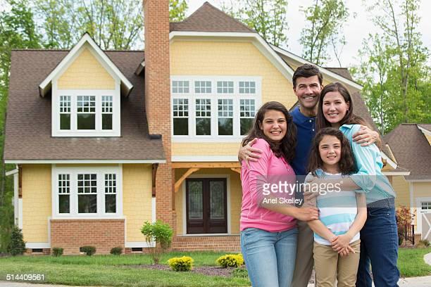 Caucasian family smiling outside house