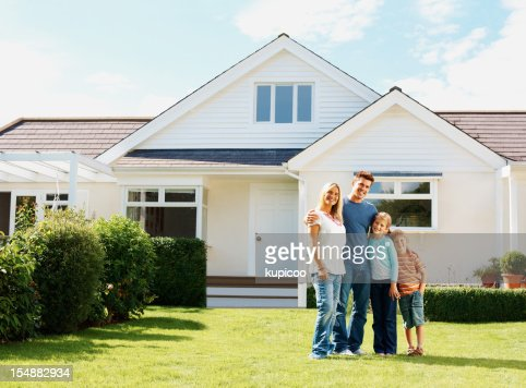 Caucasian family standing in front of a luxury house