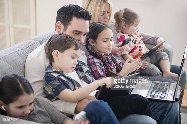 Caucasian family using technology on sofa