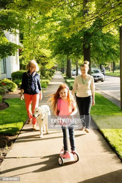 Caucasian family walking dog on suburban sidewalk