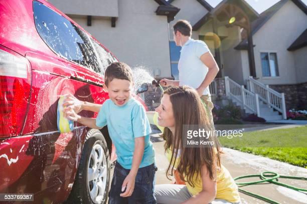 Caucasian family washing car in driveway