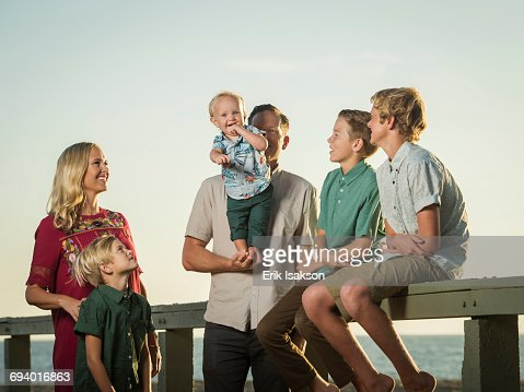 Caucasian family watching baby boy stand on hands of father