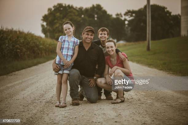 Caucasian farmer and family smiling on dirt road