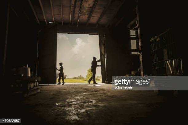 Caucasian farmer and son working in barn