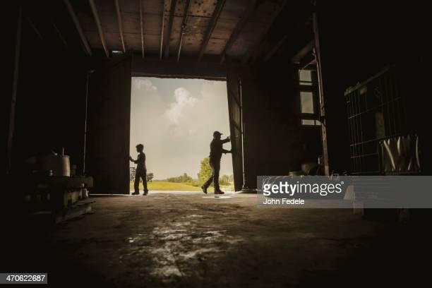 Caucasian farmer and son working in barn