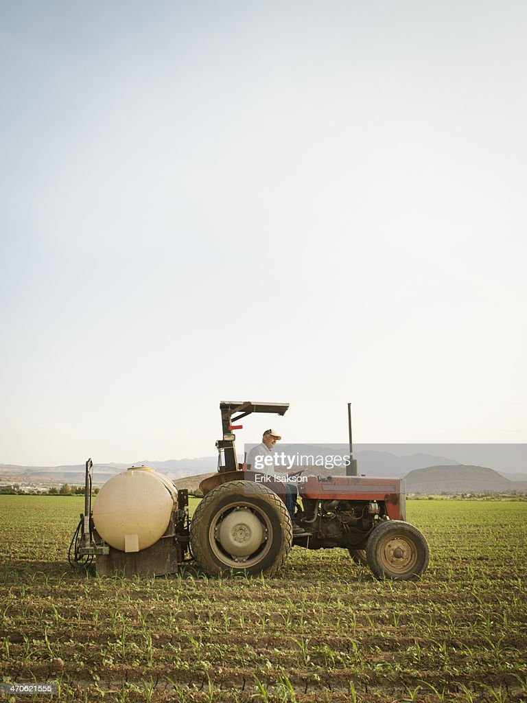 Caucasian farmer driving tractor in crop field