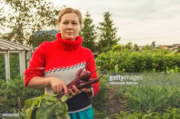 Caucasian farmer holding fresh beets in garden
