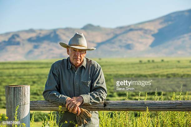Caucasian farmer holding gloves leaning on wooden fence