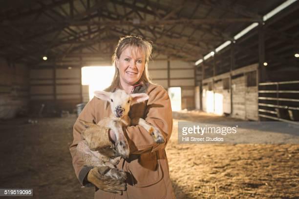 Caucasian farmer holding lamb in barn