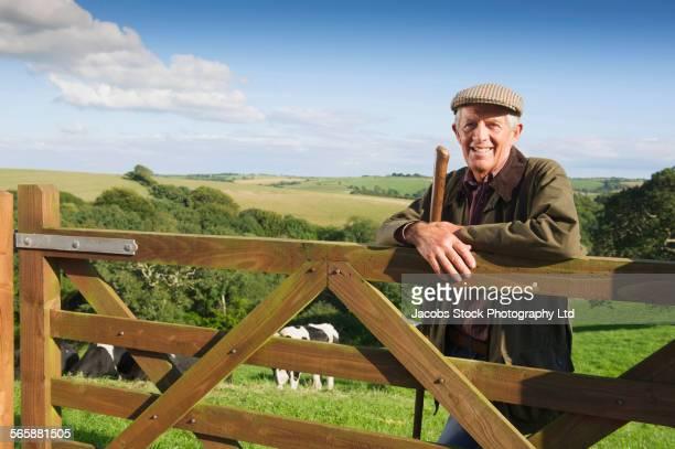 Caucasian farmer leaning on fence in rural field