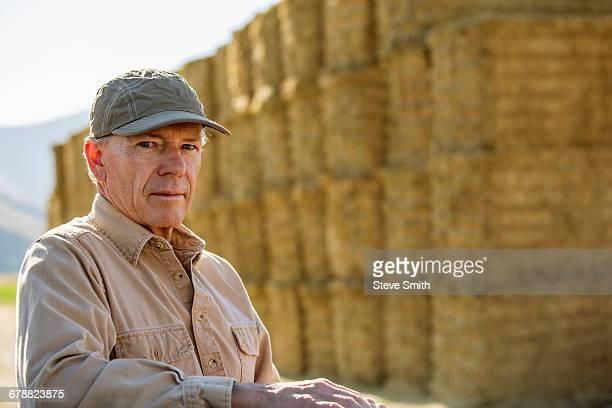Caucasian farmer near stacks of hay