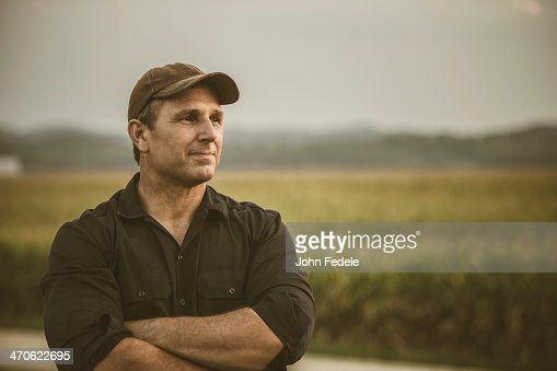 Caucasian farmer overlooking crop fields