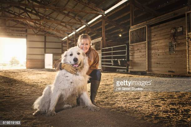 Caucasian farmer smiling with dog in barn