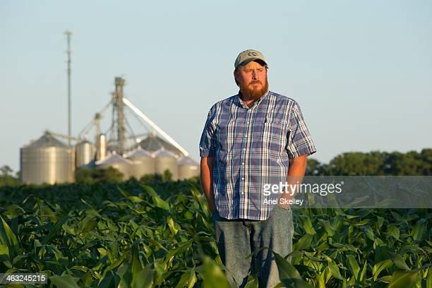 Caucasian farmer standing in crop field