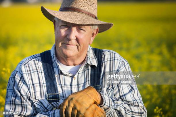 Caucasian farmer standing in mustard field