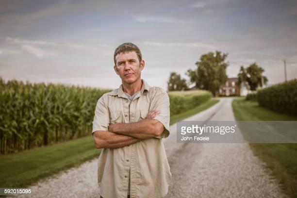 Caucasian farmer standing on dirt road by corn field