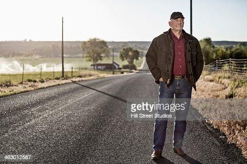 Caucasian farmer standing on rural road